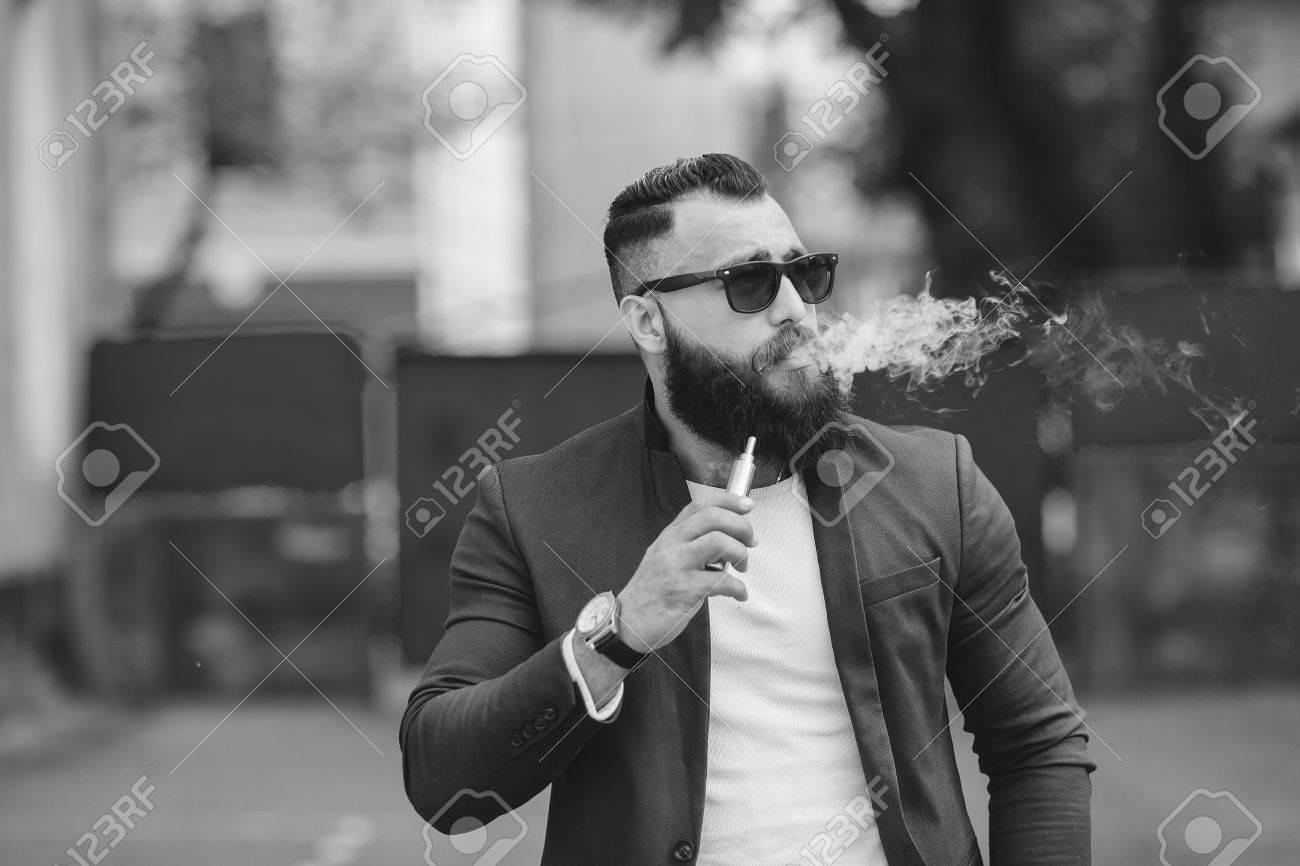 stylish well dressed man smoking electronic cigarette - 42523364