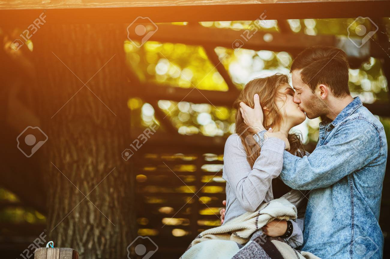 Young couple in love wrapped in plaid standing and kissing - 43523788