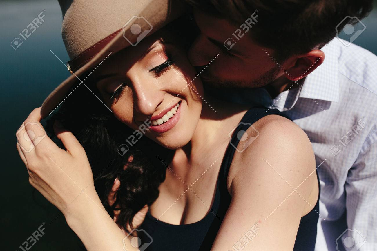 beautiful young couple spends time on the wooden pier on the lake - 43934101
