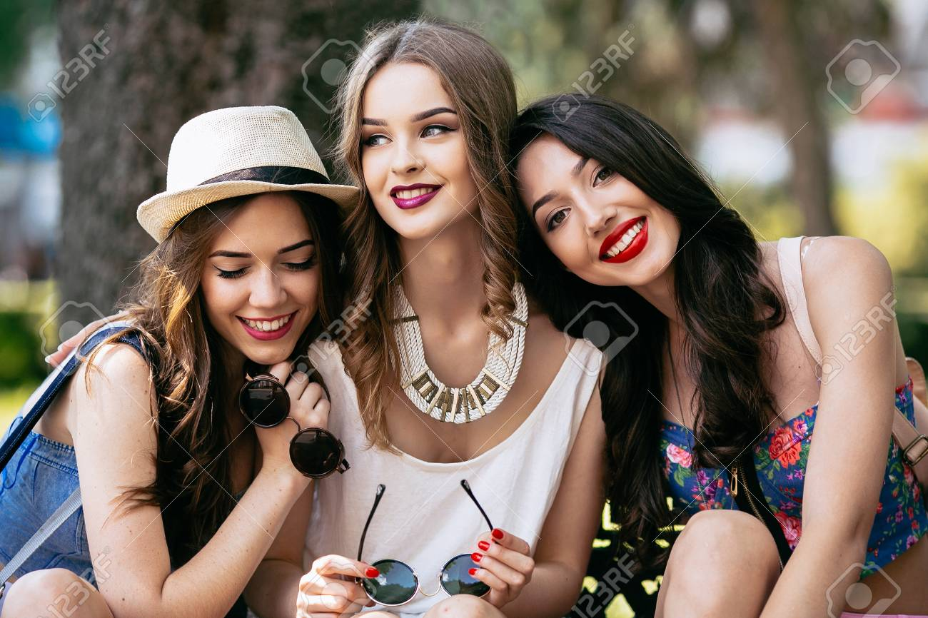 Three beautiful young girls posing against the backdrop of the park - 44421574