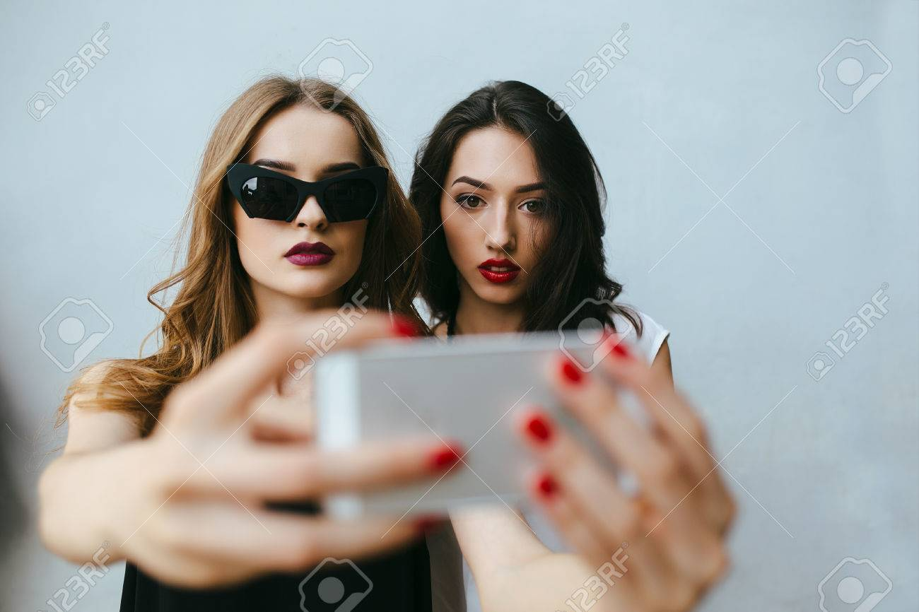 Two teenage girlfriends taking a selfie with smartphone - 44751623