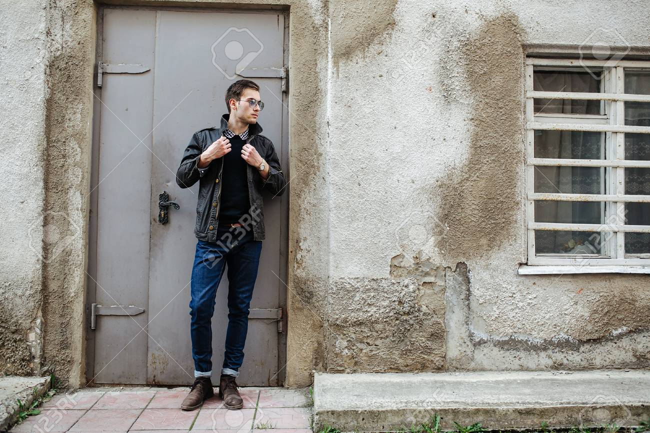 A man dressed in jeans on the background of doors - 45391171