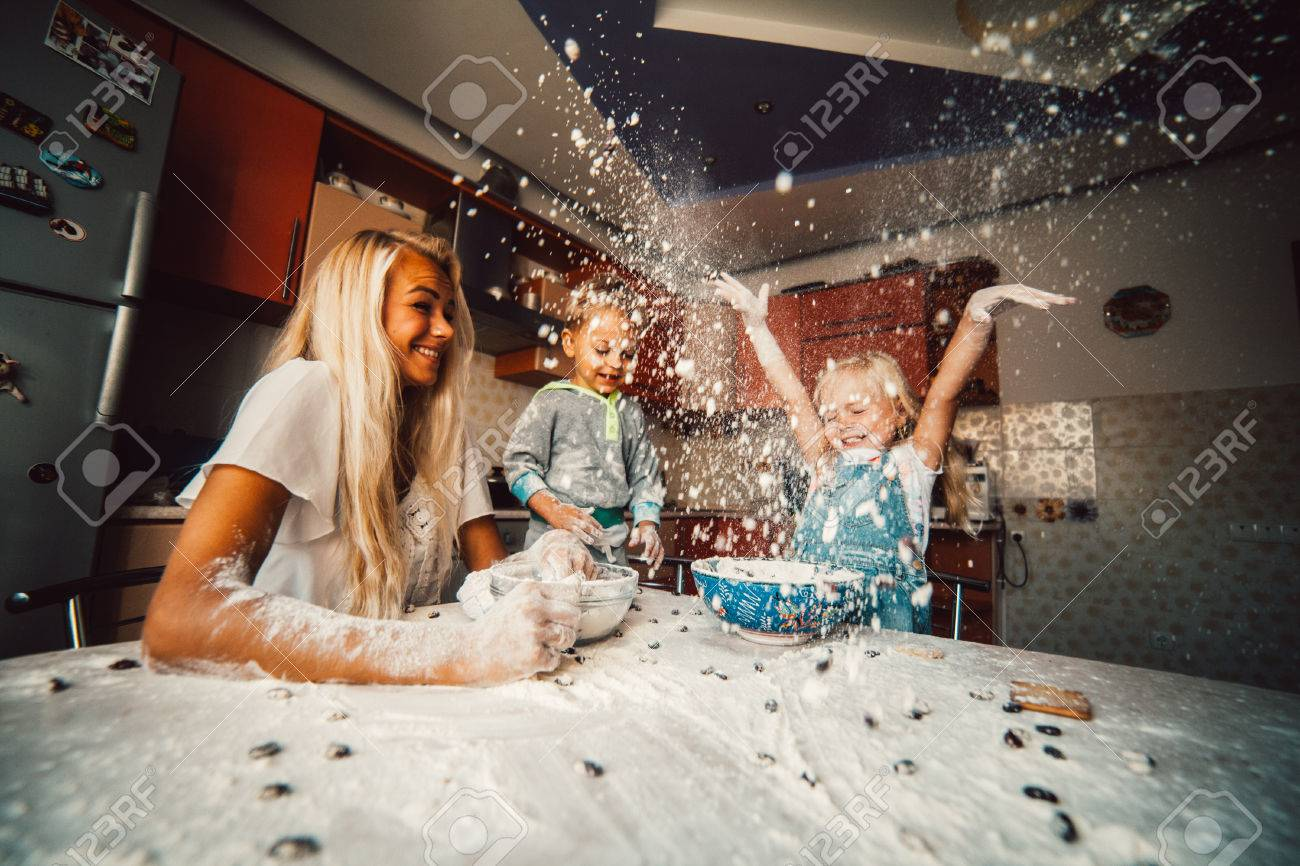 mother and children playing on kitchen with flour - 46509325