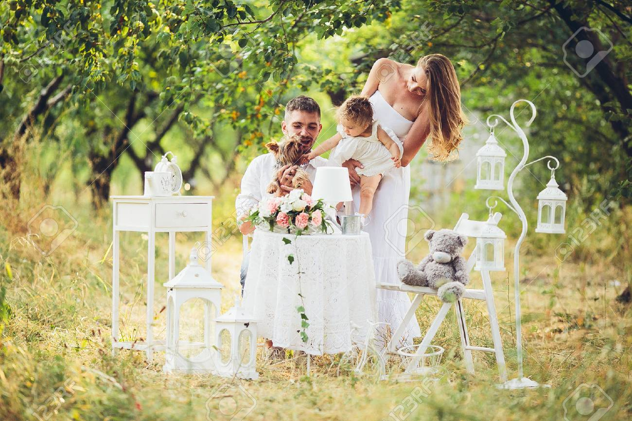 father, mother and daughter together at the picnic in the garden - 48556492