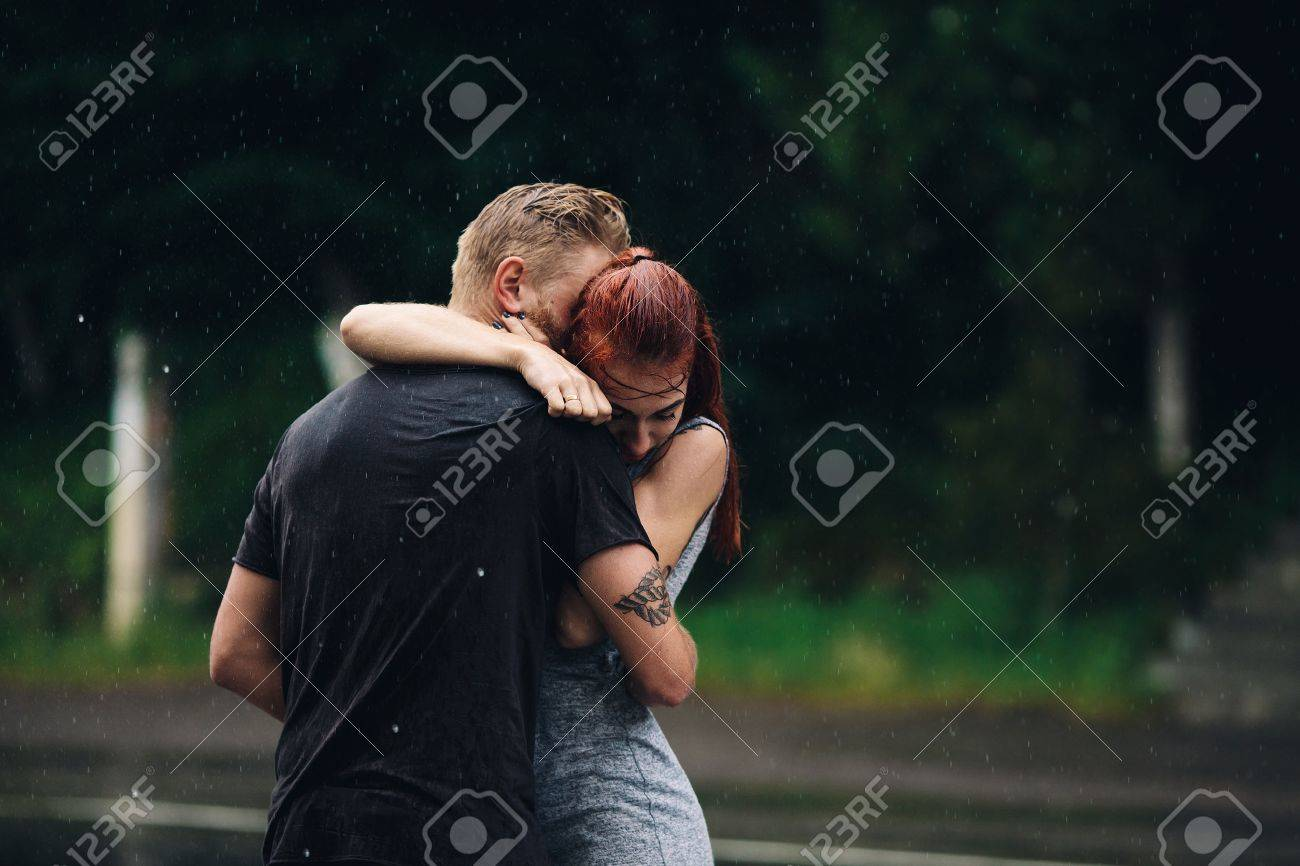 beautiful couple hugging on outside in the rain - 49612042