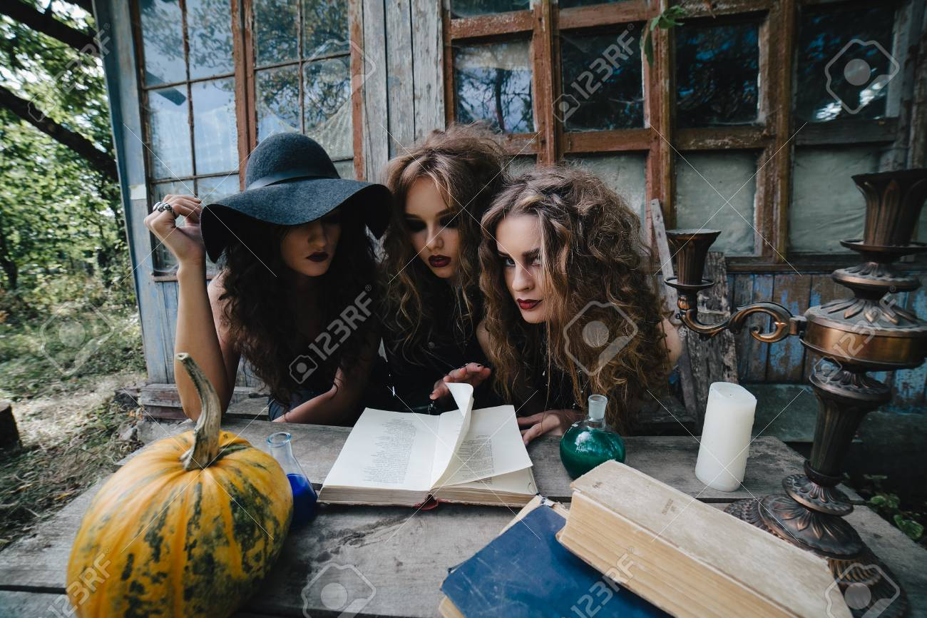 Three vintage witches perform magic ritual, at the table, reading