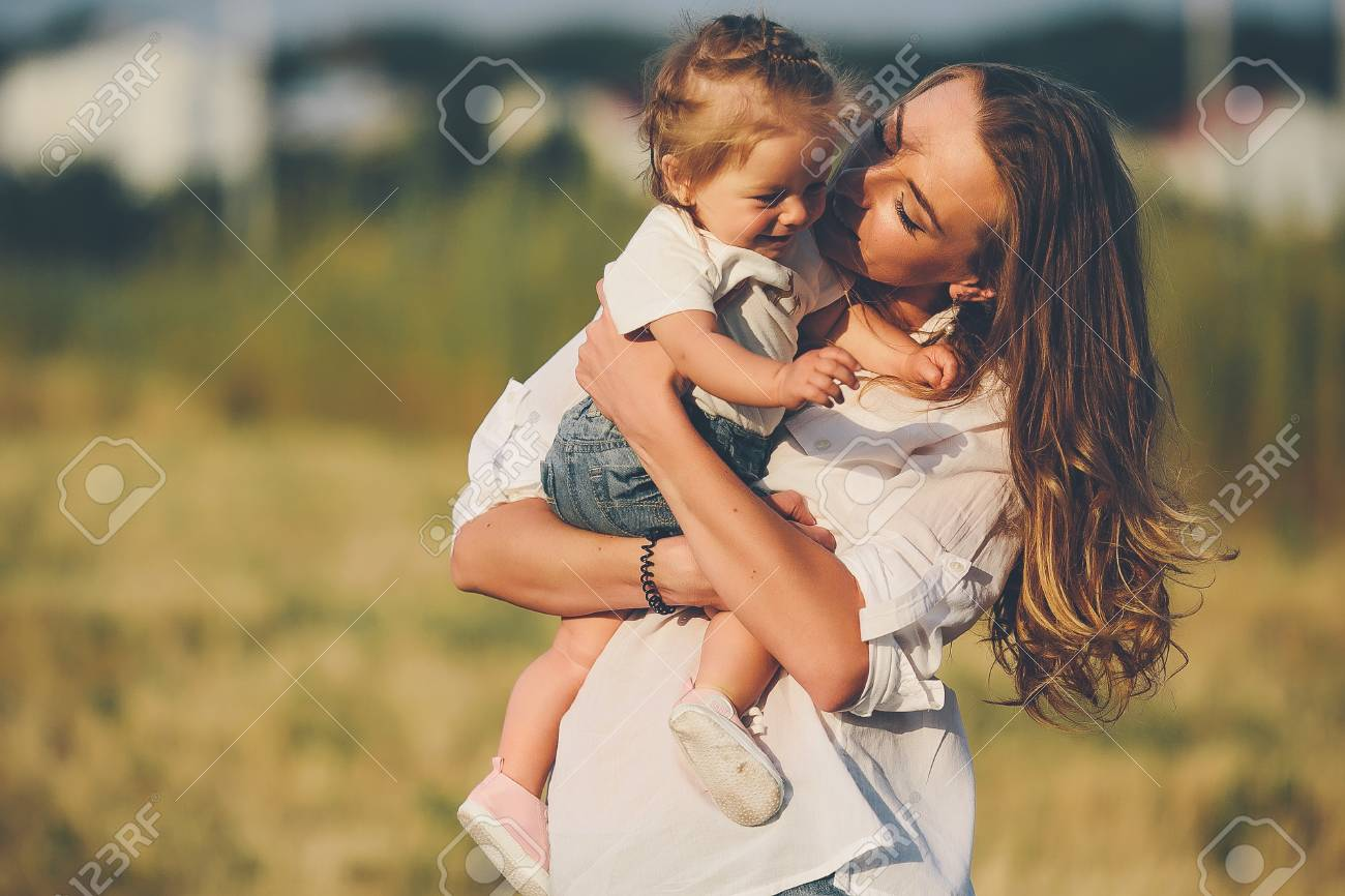mother and daughter walk together on a rural road - 58848453