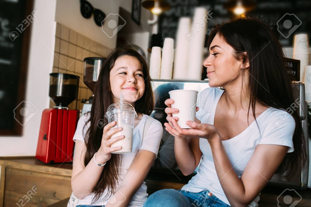 mother daughter drink espresso in the cafeteria - 61810057