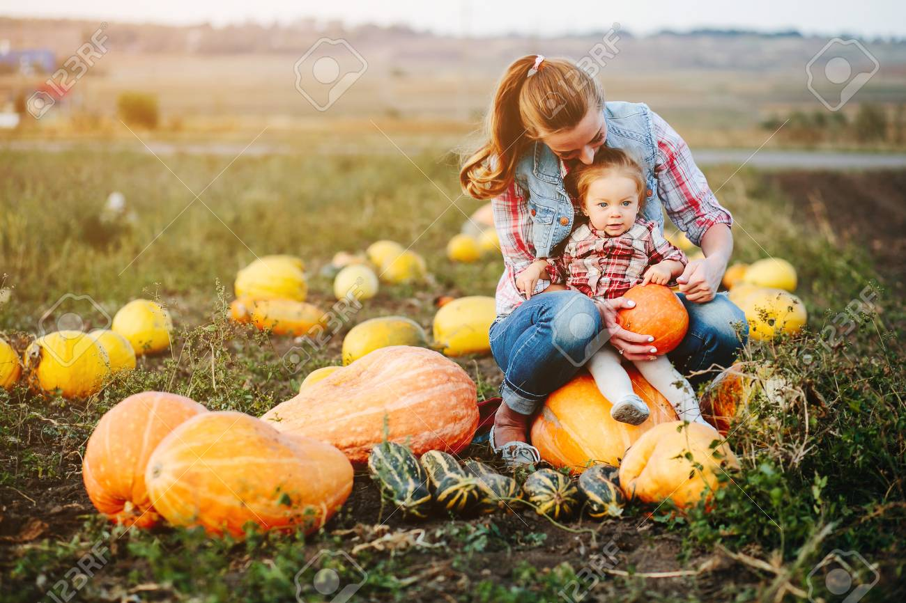 Mother and daughter sitting on pumpkins, Halloween eve - 62636679