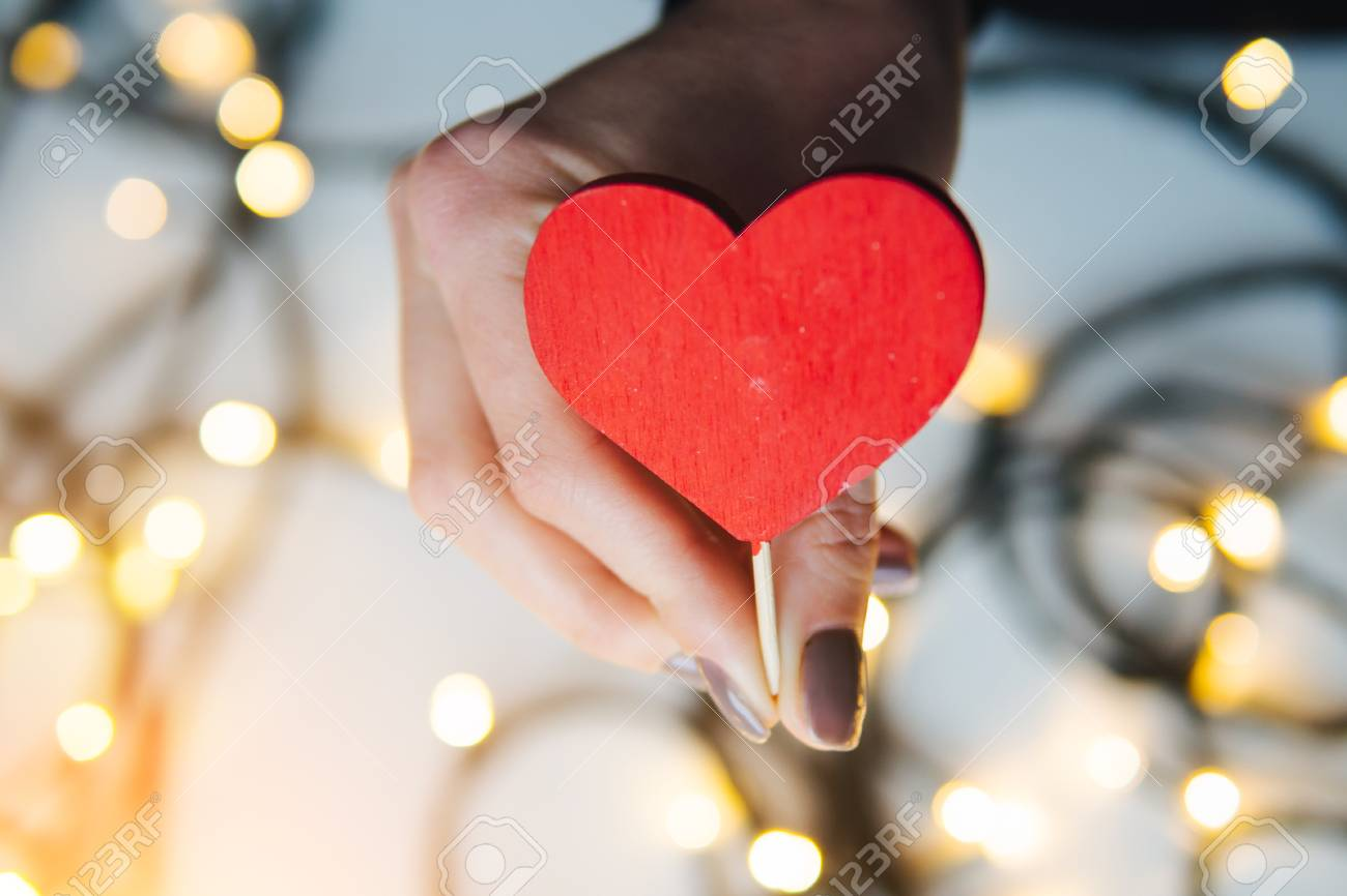 girl holding a red heart in the hands - 71508328