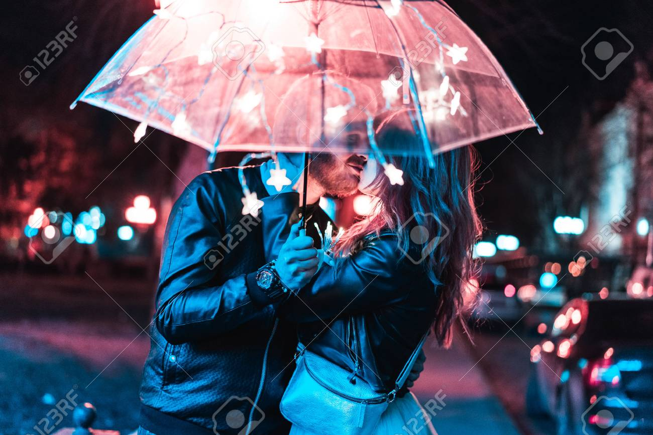 Guy and girl kissing under an umbrella - 79660399