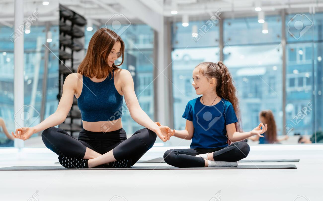Young adult mother and little daughter together practicing yoga - 126619517