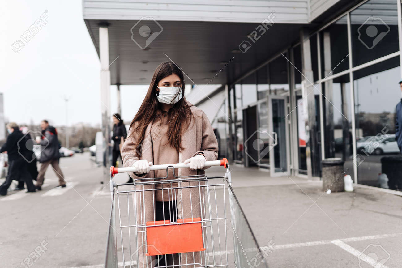 Young woman wearing protection face mask against coronavirus 2019-nCoV pushing a shopping cart. - 144659950