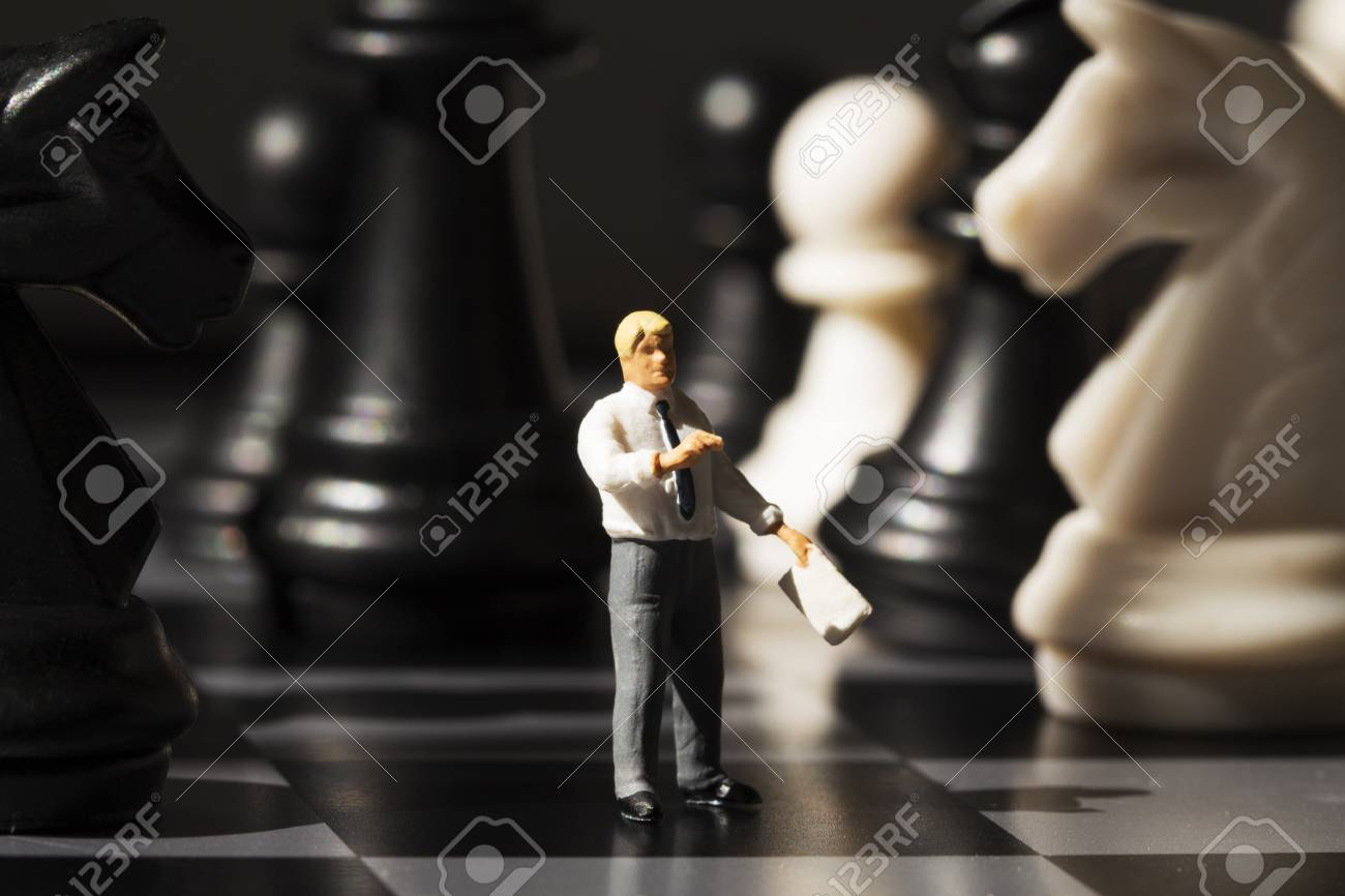 Miniature teacher explains chess game rules on board  Chess strategy