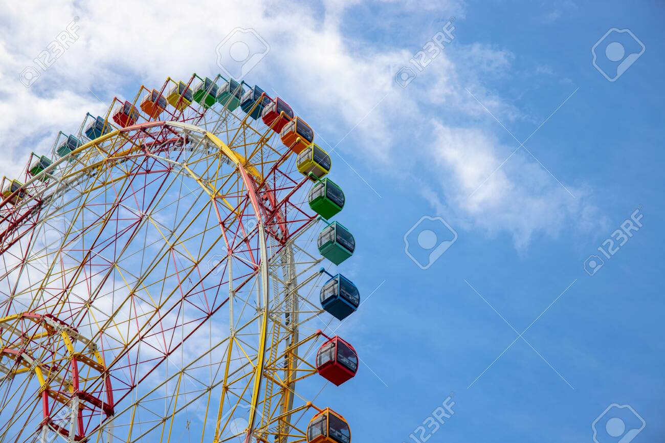 Ferris wheel on blue sky background. Ferris wheel attraction in summer park. Orange metallic construction of attraction. Colorful car on ferris wheel. Summer holiday in adventure park. Kids weekend - 130910149