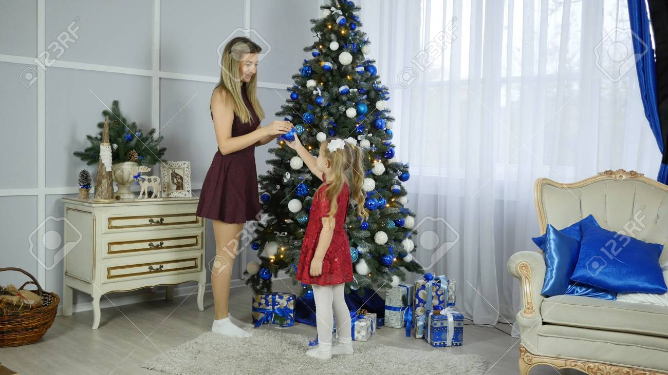 Mom and daughter decorate Christmas tree - 89970781