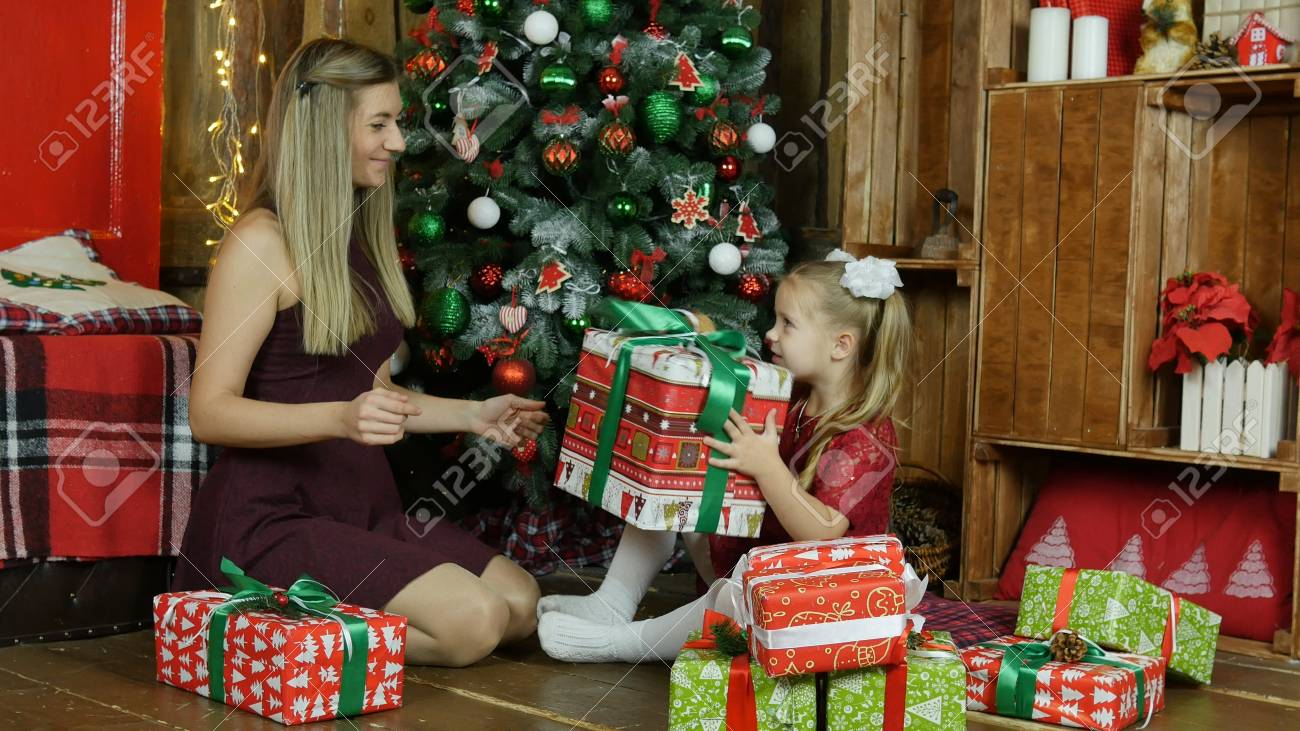 Mom and daughter give presents for the new year - 90105446