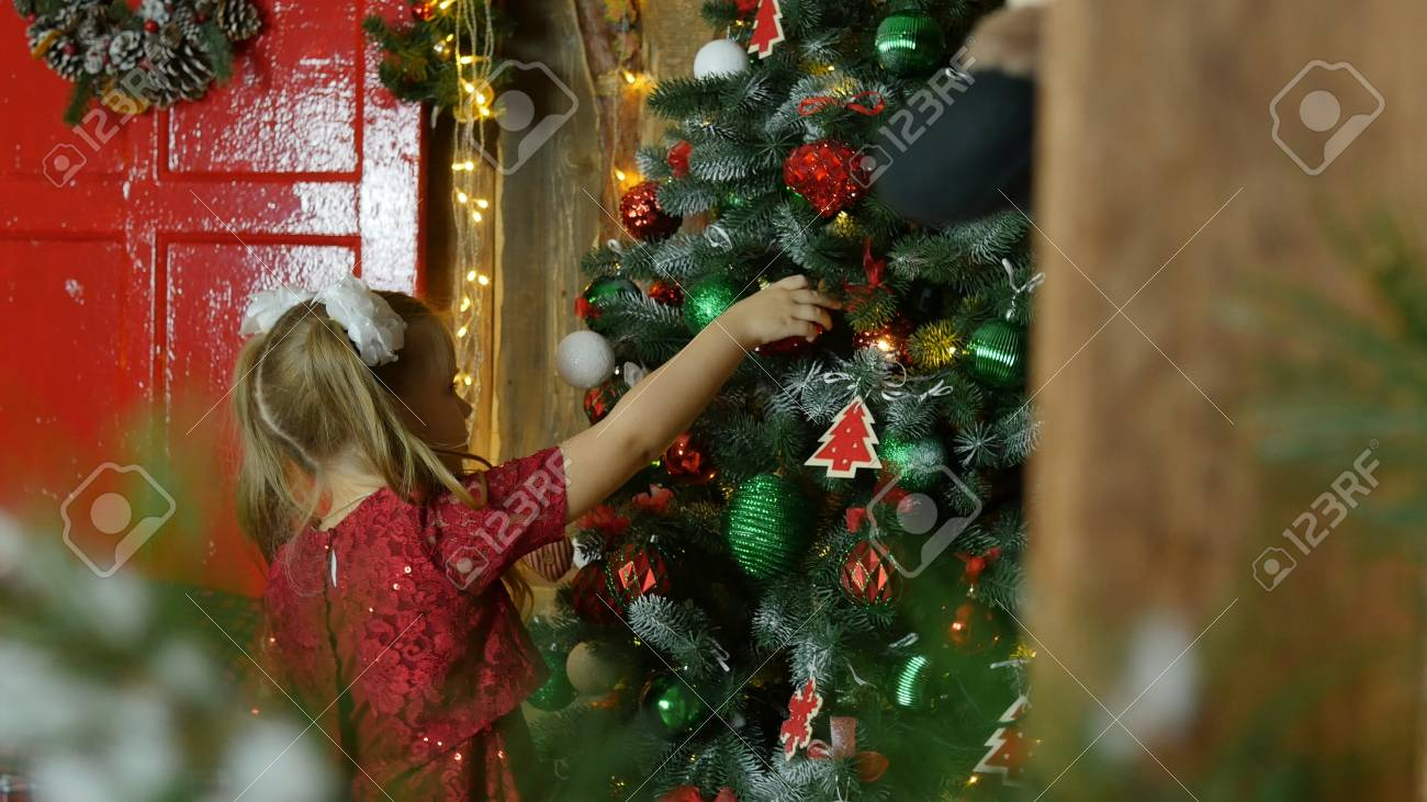little girl hanging on the Christmas tree toys - 90034560