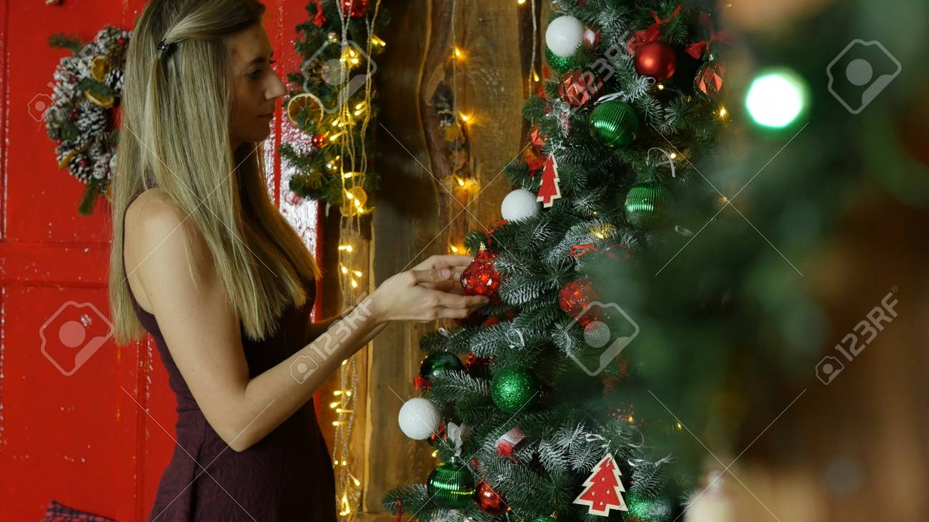 young girl decorate Christmas tree - 90105448