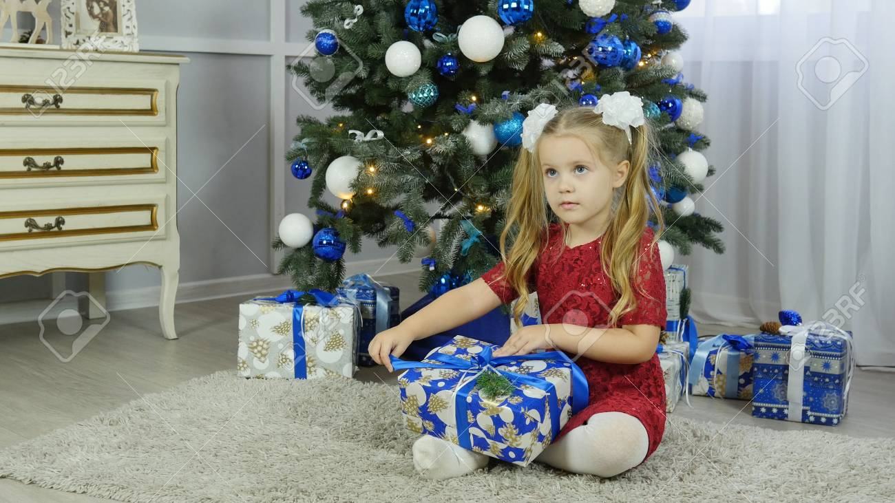 a little girl in a blue dress unpacks a New Years gift under a Christmas tree - 90105450