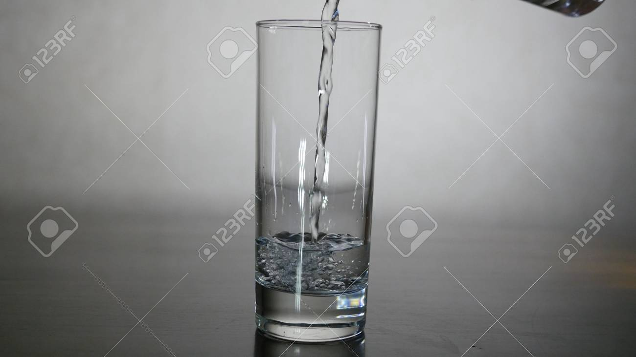 Pouring water from filter pitcher in glass on white background - 90261011