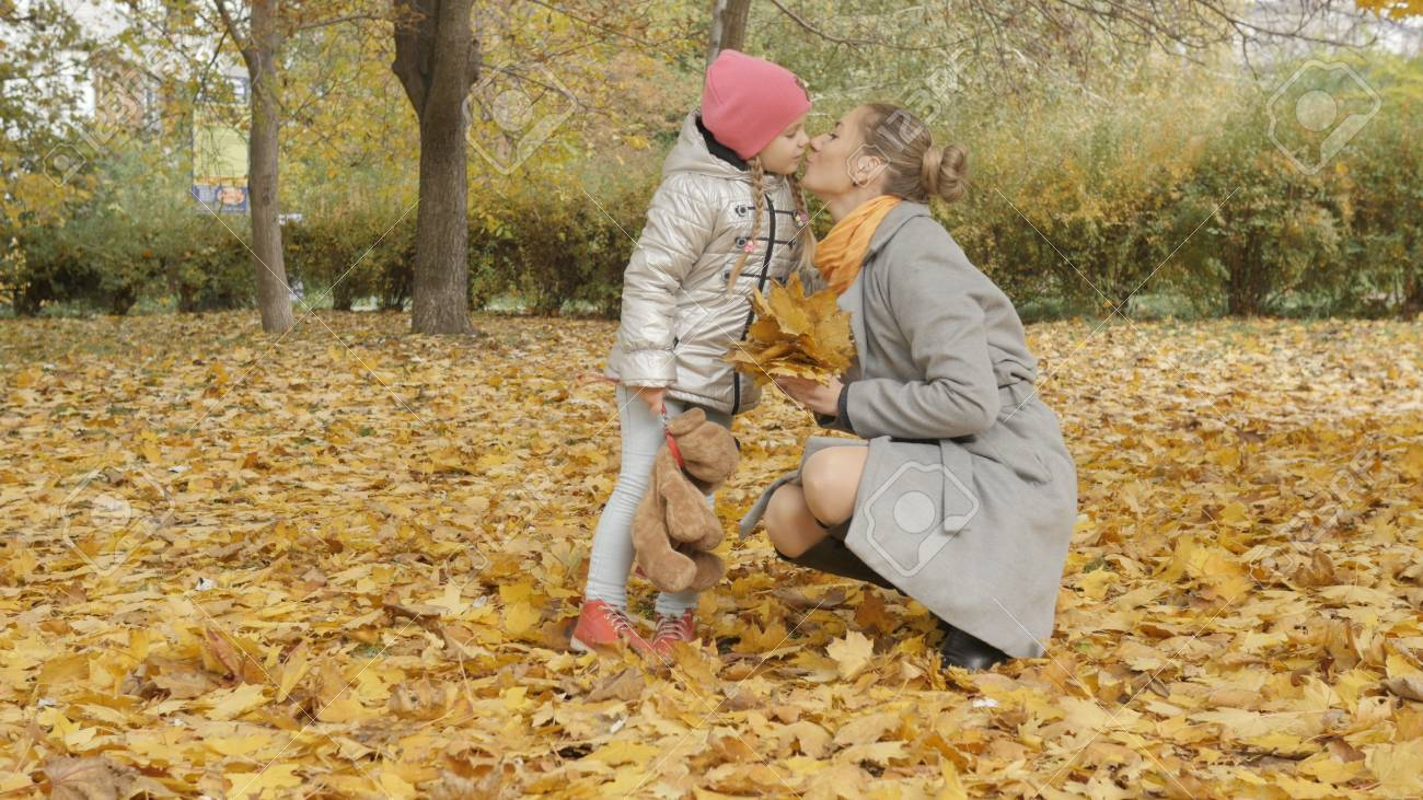 Mom and baby collect yellow fallen leaves in the park - 90469335