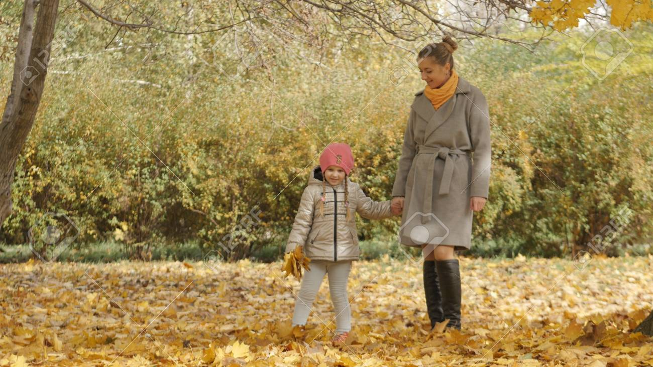 mother and daughter on a walk in the autumn park. Walking together in the autumn forest. Yellow fallen leaves - 90527347