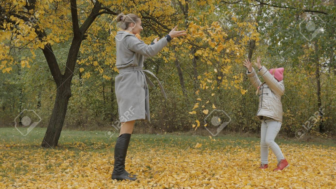 Mom and daughter throw yellow leaves - 90527349