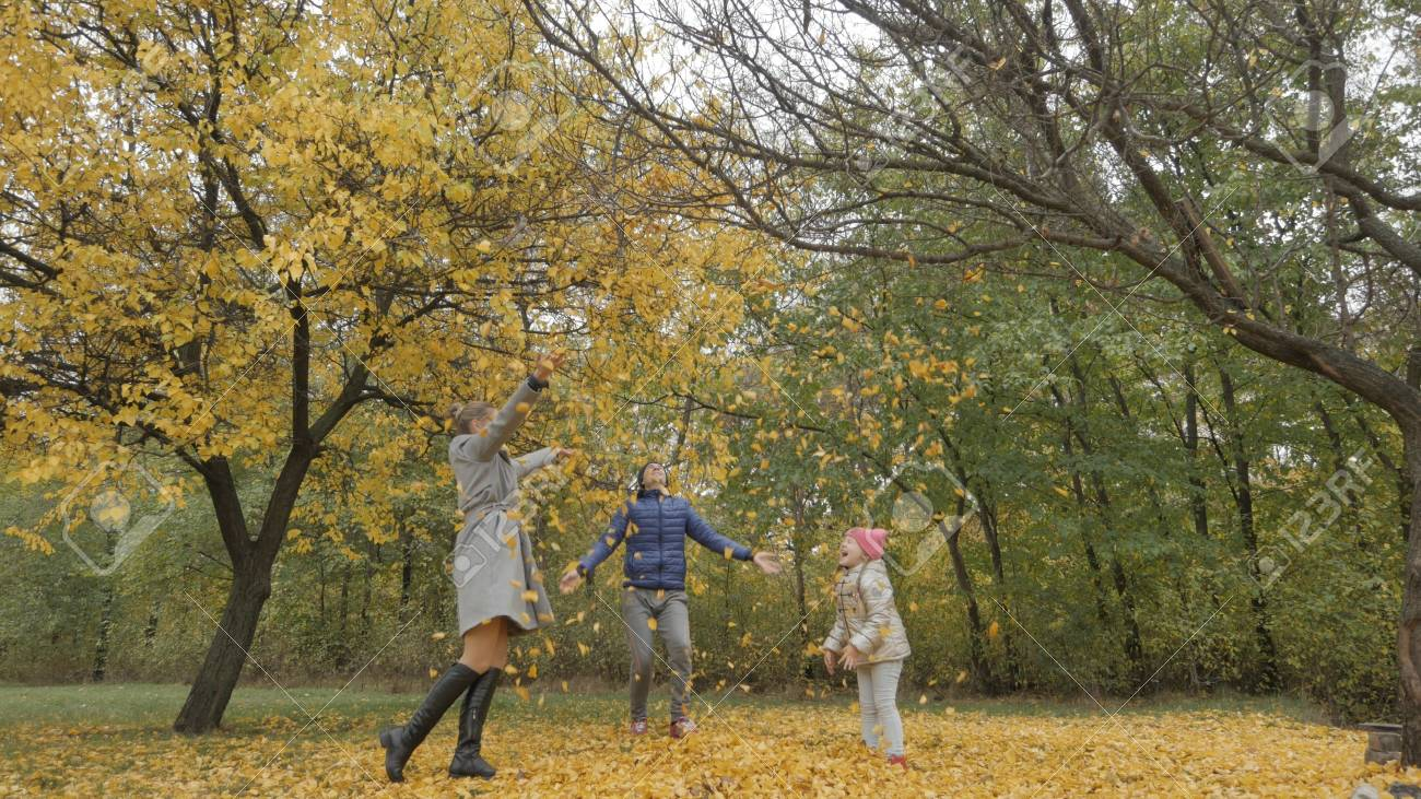 daddy turns child in autumn park. dad twirling a child on a background of yellow leaves - 90539375