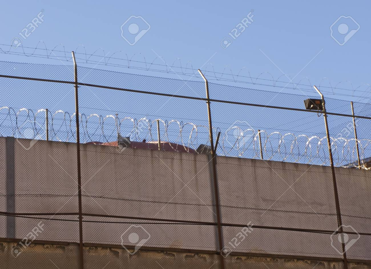 Barb wire into a prison wall, detail Stock Photo - 11739728