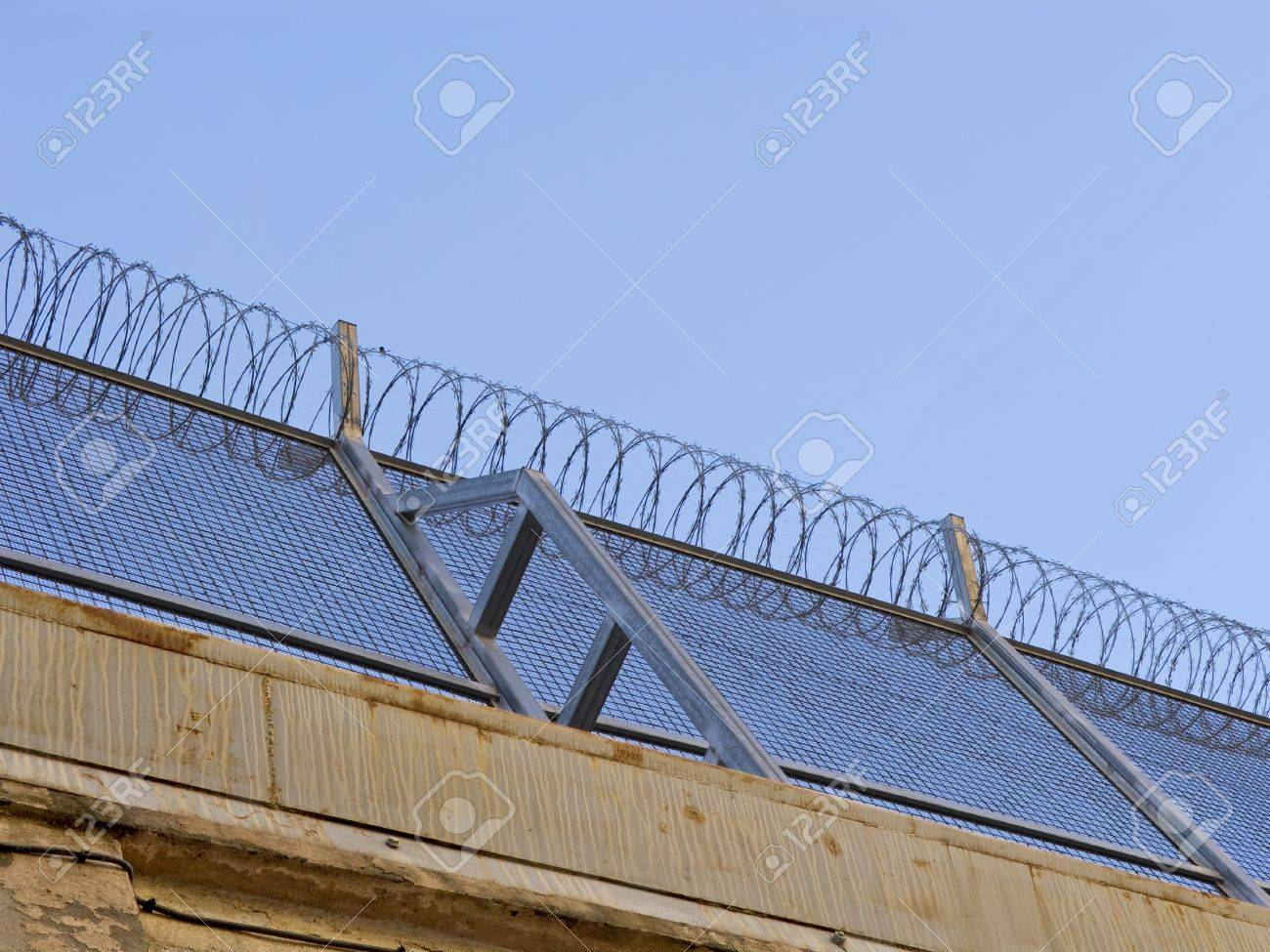 Barb wire into a prison wall, detail Stock Photo - 13379733