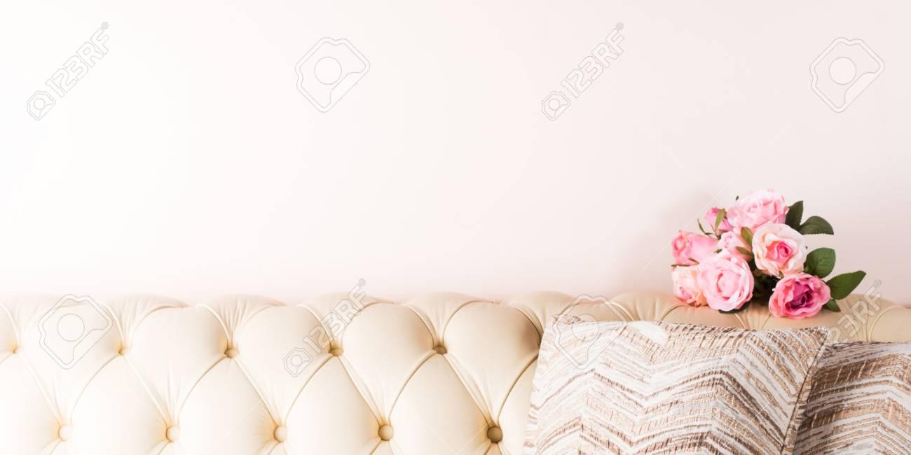 Canapé Fleur De Cuir fond de canapé en cuir blanc crème avec des oreillers et des fleurs
