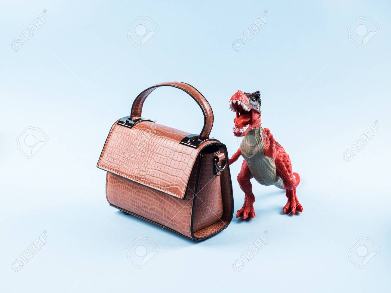 Angry dinosaur toy and lady hand bag. Fashion concept. Sale - 145339066