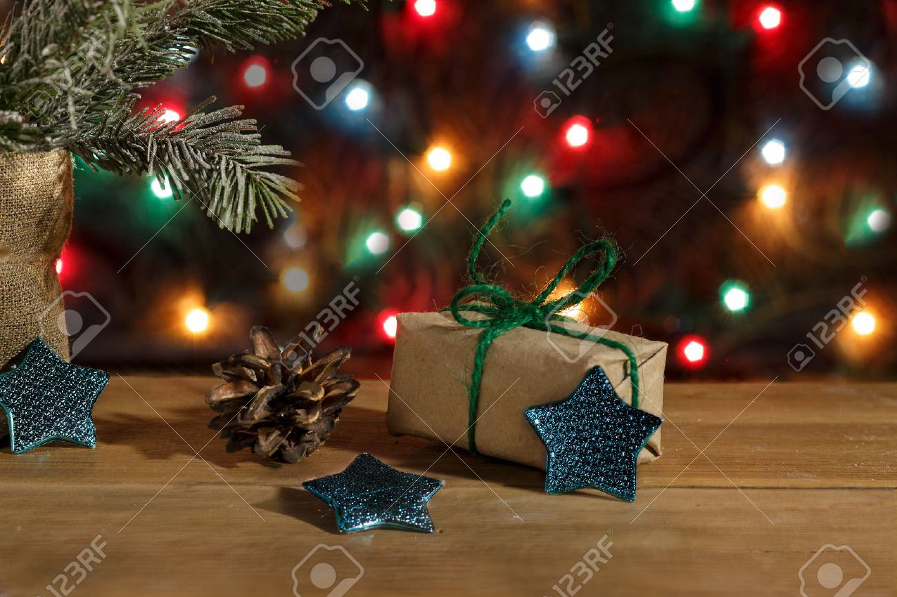 New Year gift box in wrapping paper, stars and pinecone on background of lights garland Standard-Bild - 89923022
