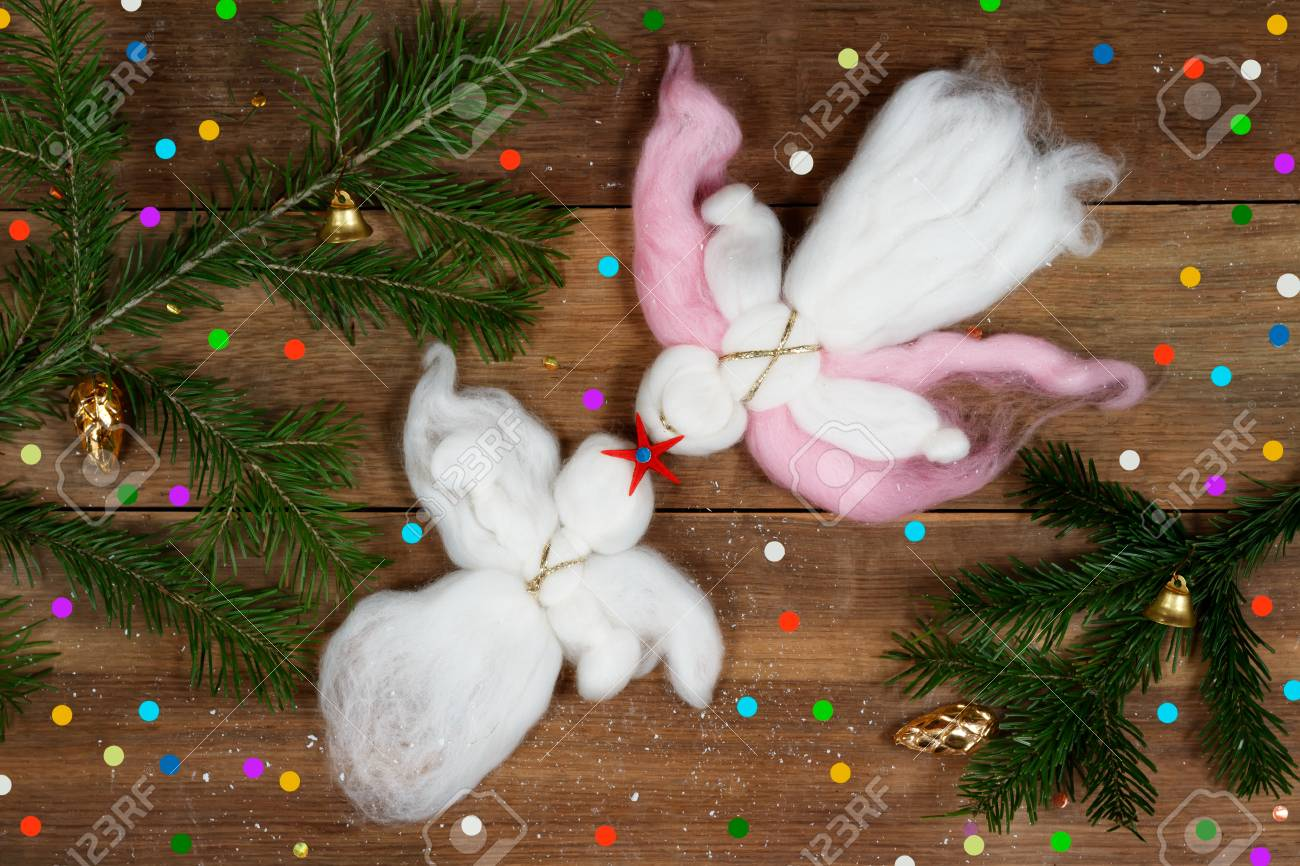 Christmas card: two white woolen angels, red star, colorful confetti and evergreen branches on wood plank. Standard-Bild - 89950752