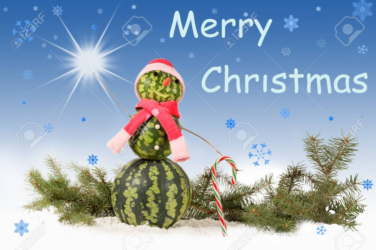 made from watermelon Snowman  in red hat and scarf with candy cane on blue background and falling snowflakes. Holiday concept for Christmas with  inscription and star Standard-Bild - 90815831