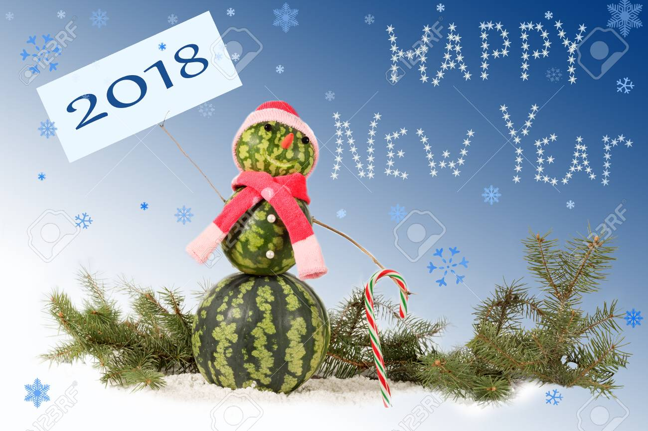 made from watermelon Snowman  in red hat and scarf with candy cane on blue background and falling snowflakes. Holiday concept for New Years with  inscription 2018 Standard-Bild - 91095824