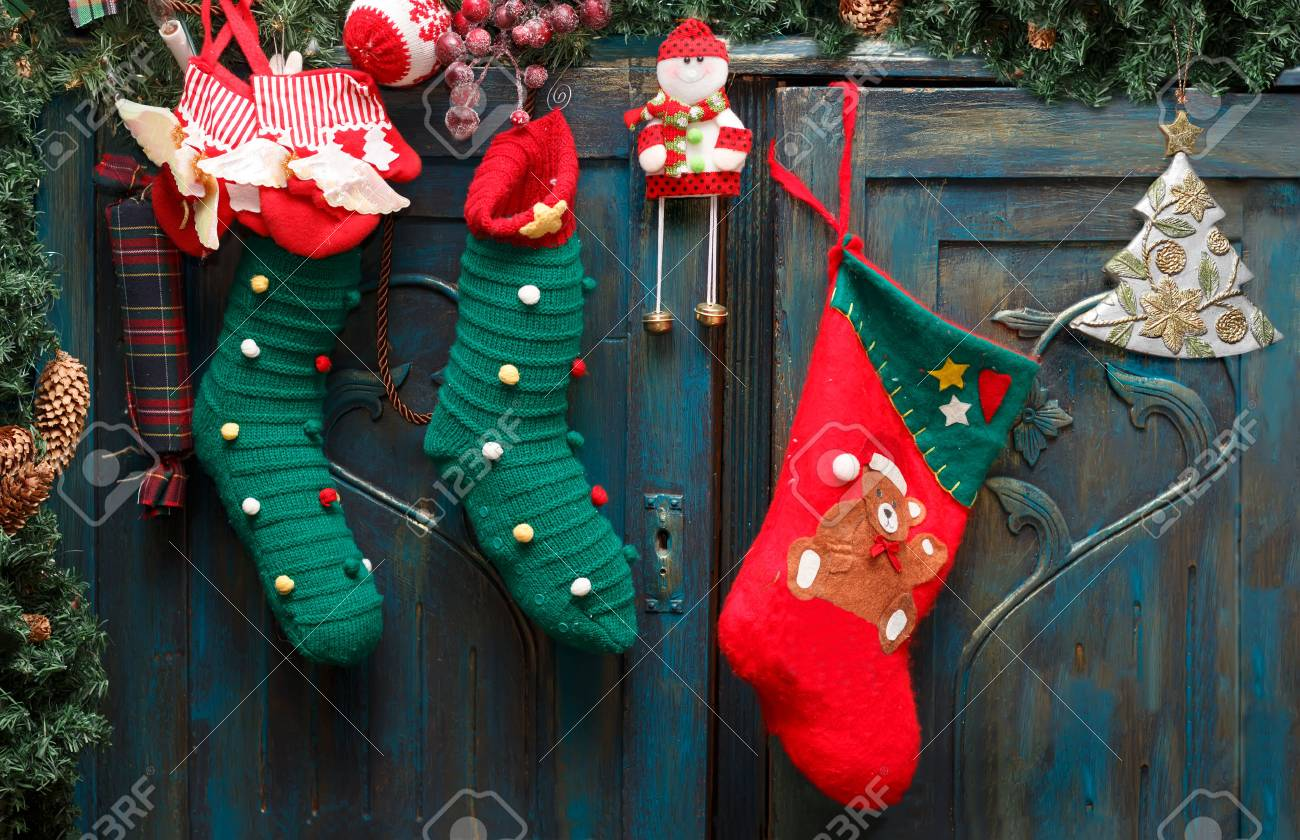 Christmas decorations: red Santa's boot, green stockings, evergreen branch with pine cones and christmas toys on blue doors of old wardrobe. Standard-Bild - 91183844