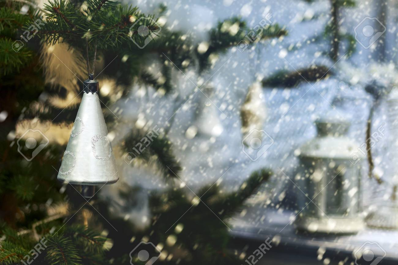 Plastic silver colored bell on an evergreen tree on a background of a snowing and a lamp on a porch. Small DoF focus put only to bell. Retro style Standard-Bild - 91436779