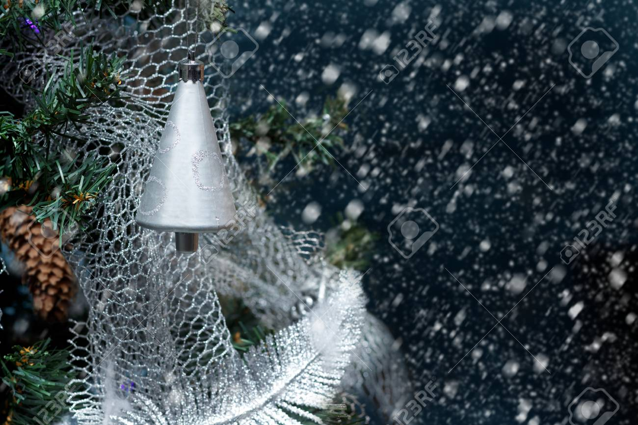 Plastic silver colored bell on Christmas tree by night on background of snowing. Standard-Bild - 91173453