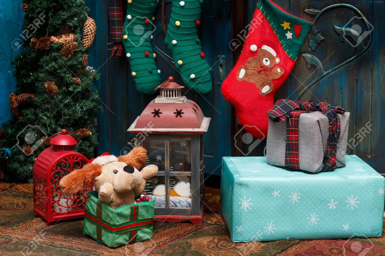 Christmas decorations: gift boxes, lamps, red boot, green stockings on the carpet near blue old wardrobe and small fir. Standard-Bild - 91331266