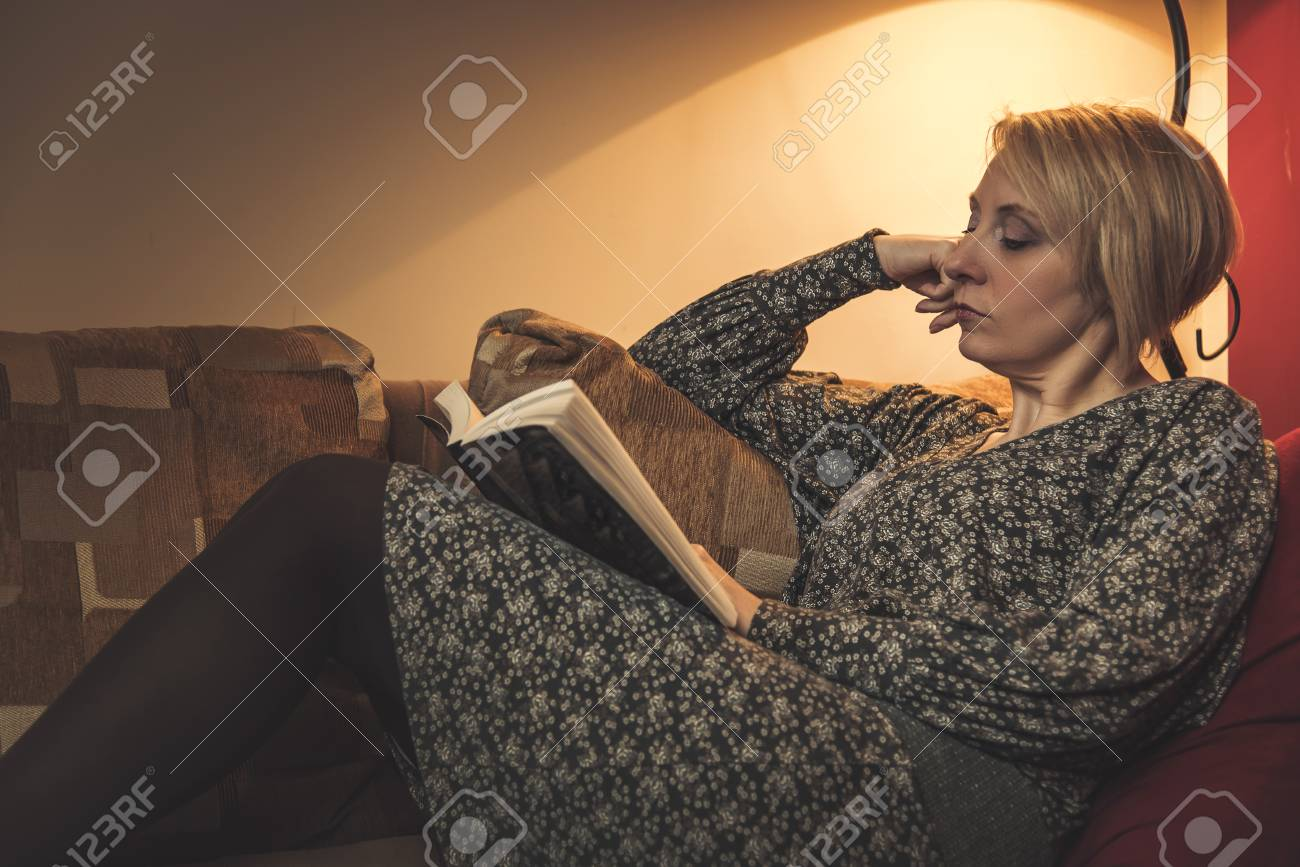 Mature blonde woman reading her favorite book, laying on a sofa in her  living room