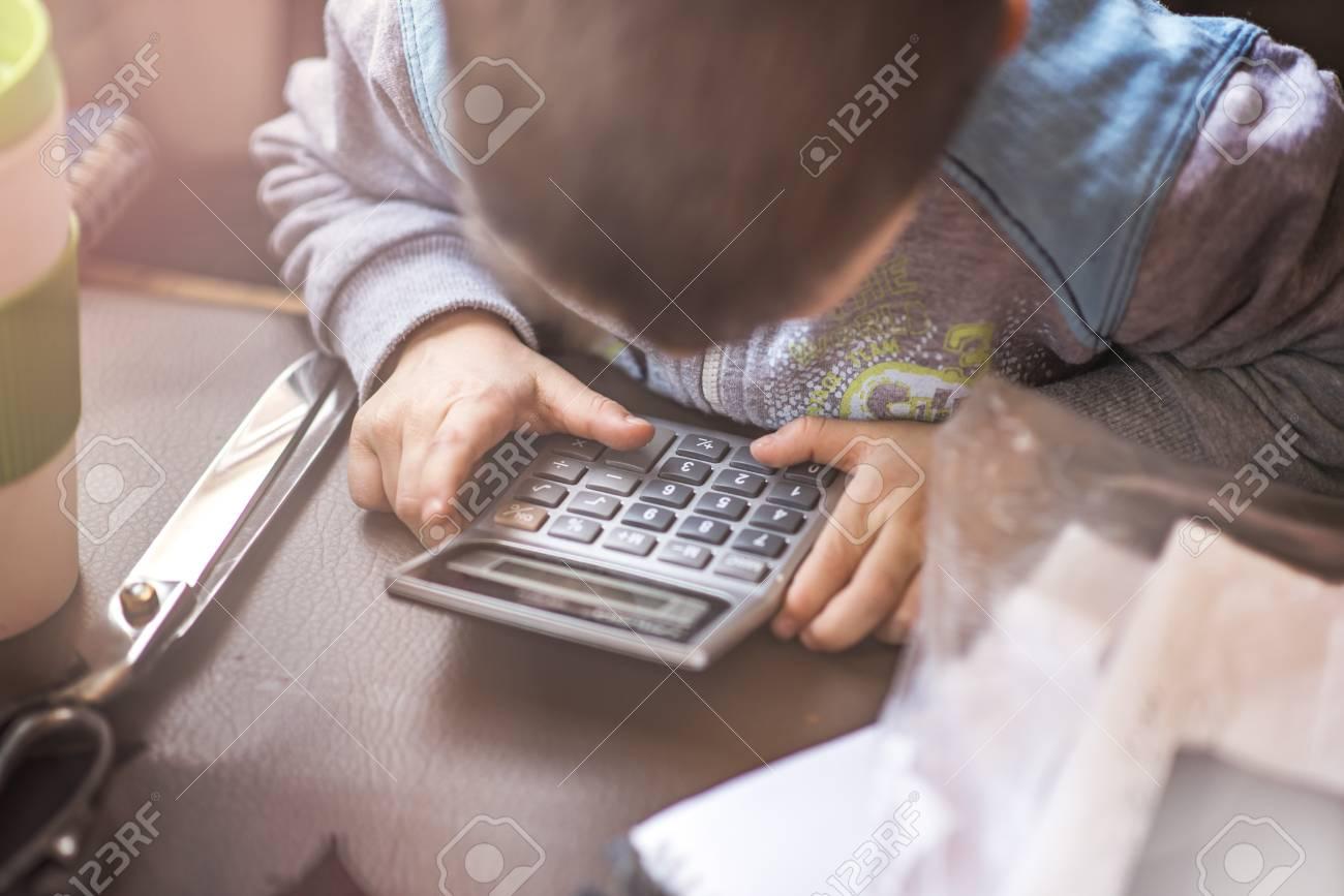 Cute Little Toddler Boy Using A Calculator, Figuring Out A Math ...