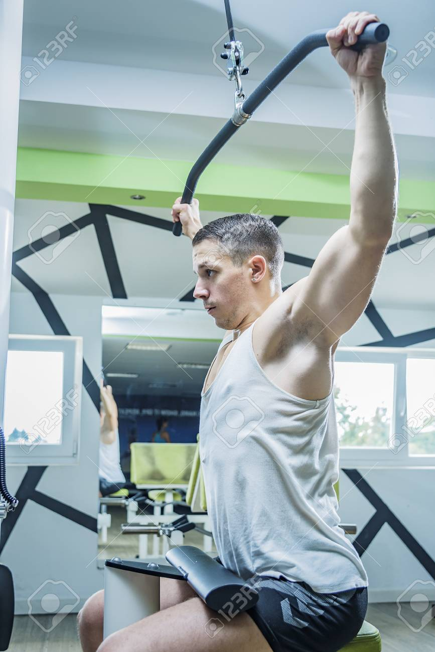 Shoulder pull down machine  Fitness man working out lat pulldown