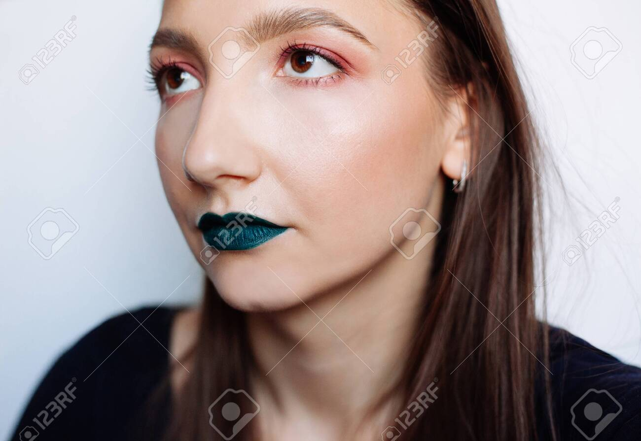 Close up selfie portrait of pretty young brunette with creative make up: green ilpstick and red eyeshadows - 122133924