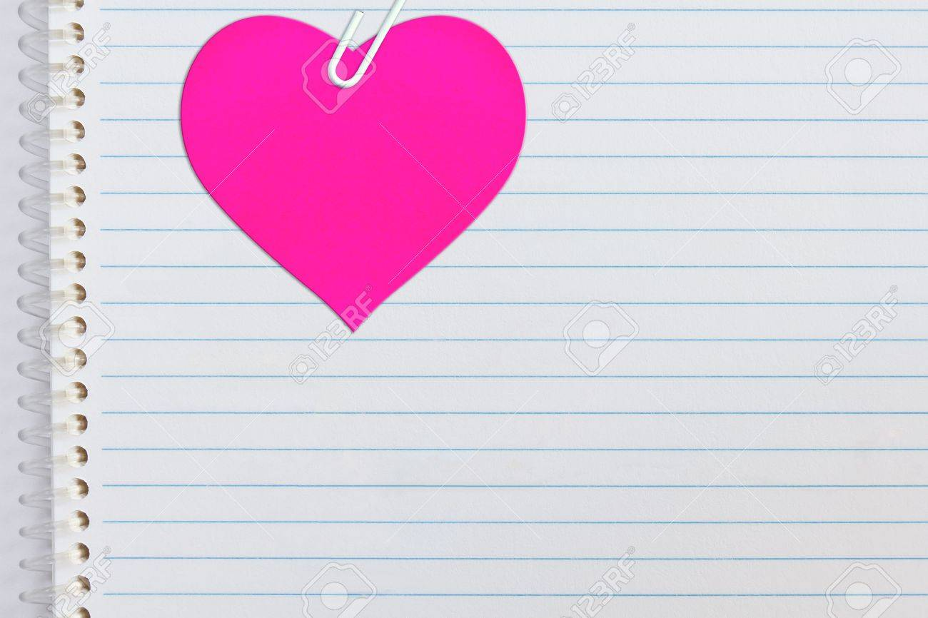 Pink heart attached on notebook paper with paperclip Stock Photo - 12220729