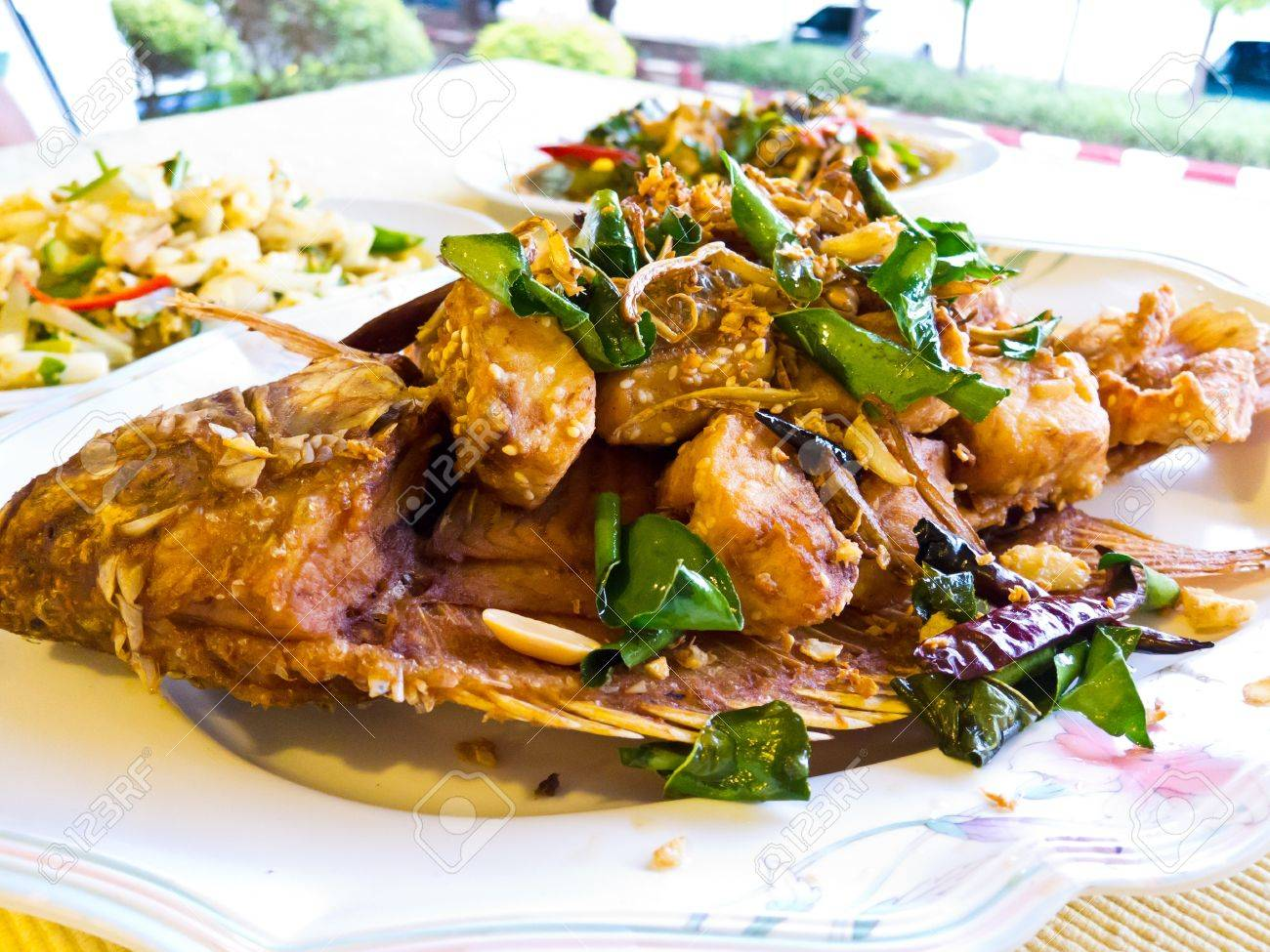 Fried mango fish  nilotica fish , topped with Thai herbs and nut Stock Photo - 13756517