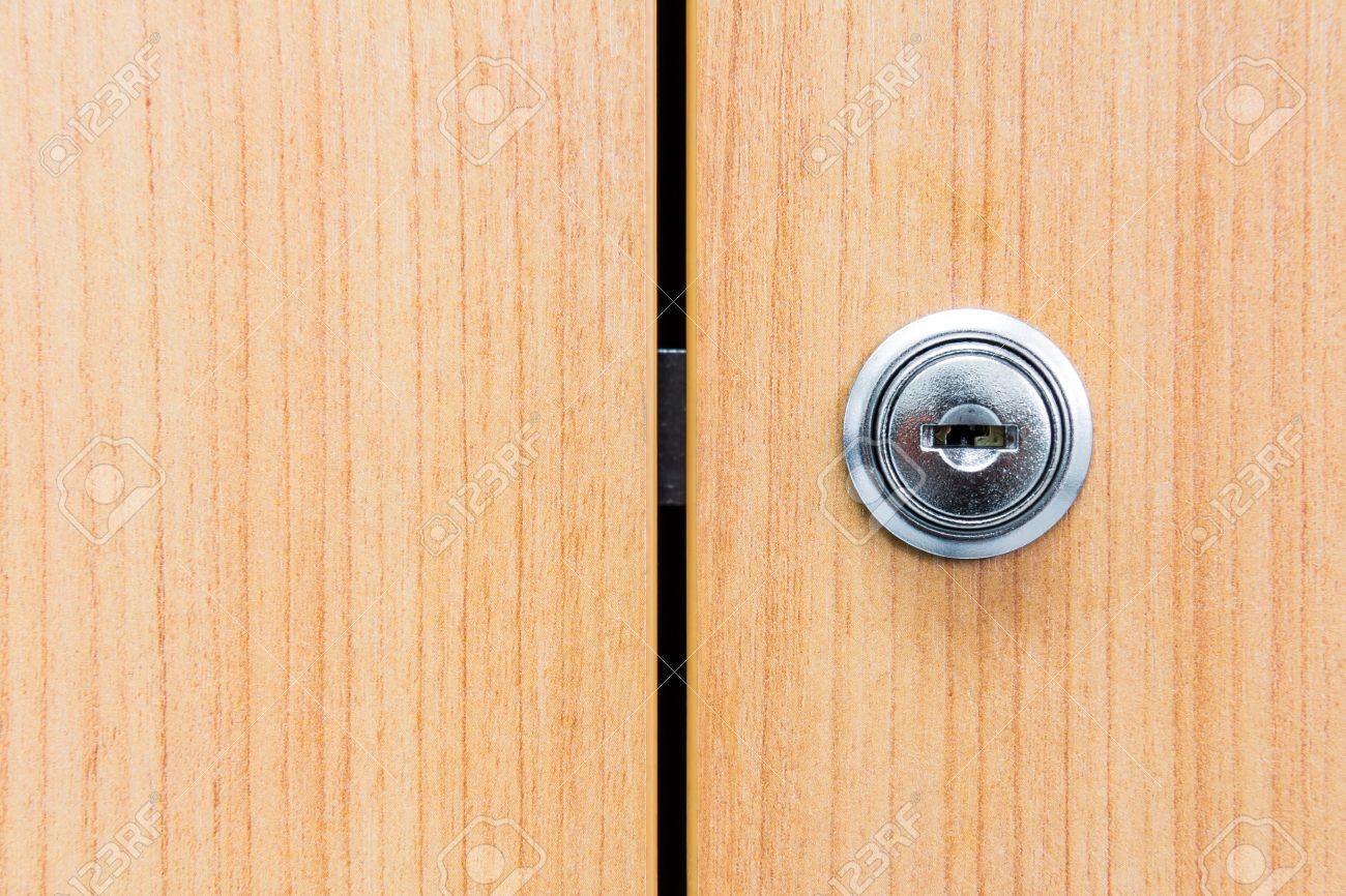 Close Up Of Locked Wooden Cabinet Door With Metallic Lock On