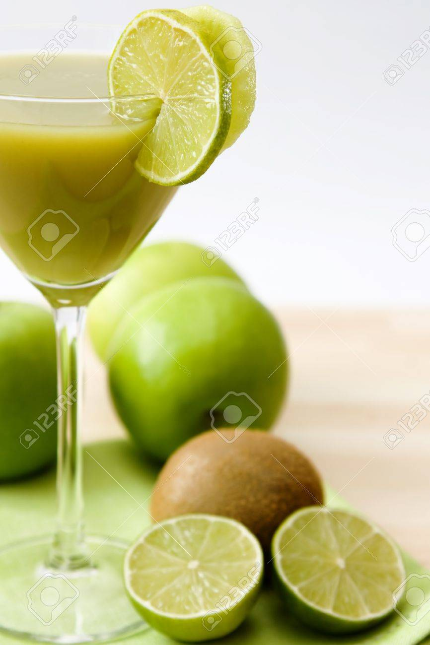 Close,up image of a glass with a green fruit juice and lime and kiwi