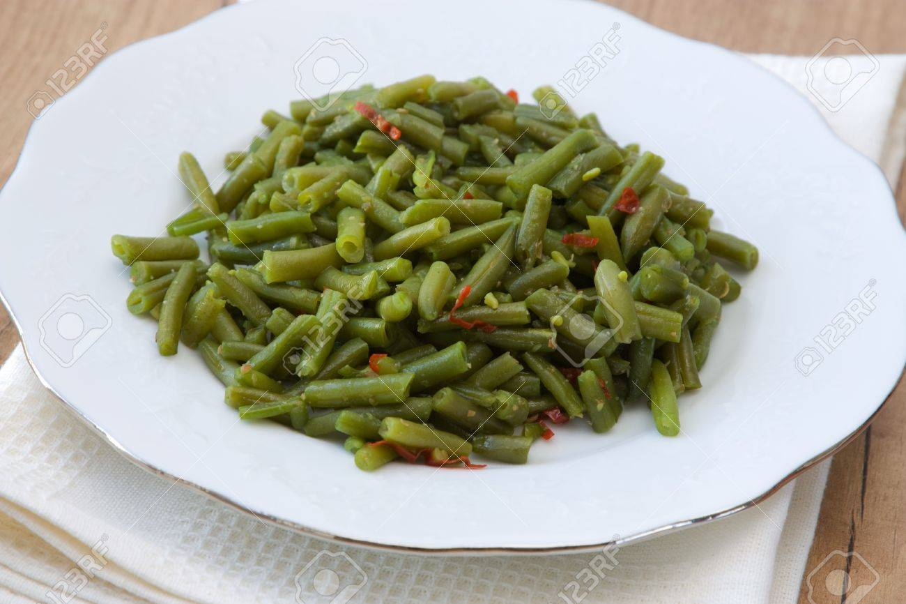 Plate with cooked green beans photographed in vintage style with old dish towel. Stock Photo - 8185195